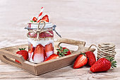 Strawberry fruit dessert with low fat yogurt,  chia seeds and puffed quinoa grains layered in jar surrounded by berries on wooden background