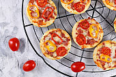 Small mini pizzas topped with cheese, tomato, yellow and red bell peppers and salami sausage on round black grid side
