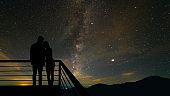 The romantic couple standing on the balcony on the scenic starry sky background