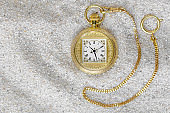 Macro photography of a old gold pocket watch on sand