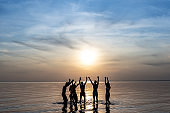 The group of people dancing on the water against the beautiful sunset