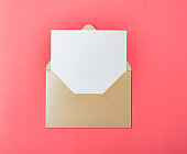 Opened gold envelope with white paper on a red background.