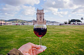 Glass of red wine in hand of traveler past the 16th century tower Belem, Lisbon of Portugal. Beautiful landscape and popular trip destination