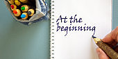 Hand writing 'at the beginning', isolated on blue background. Bag with pencils.