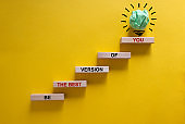 Business concept growth success process. Wood blocks stacking as step stair on yellow background, copy space. Words 'be the best version of you'. Conceptual image of motivation.