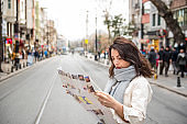 Cute girl explores streets of city with map