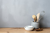 Kitchenware on a wooden table against a gray background