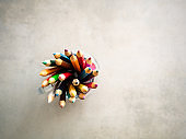 Top view of colored pencils on a gray school desk