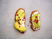 Two wholemeal bread slices with fresh avocado and pomegranate seeds on a gray table, top view