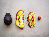 Whole grain bread with fresh avocado and pomegranate seeds in a row on a gray kitchen table, whole avocado and a core