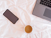 Laptop, smartphone and a cup of coffee on a white bedspread