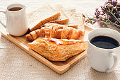 Traditional Breakfast Natural Vegetarian Food With Sourdough Bread, Coffee, Honey, Croissant on The Table., Homemade Freshly Baked French Sourdough Loaf for Breakfast. Food and Beverage Concept