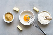 Baking ingredients in three white bowls and pieces of butter on a kitchen table