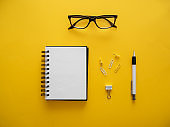 A blank notepad, reading glasses and office supplies on a yellow background, top view