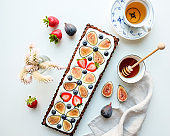 Fig and berry tart with honey and a cup of tea