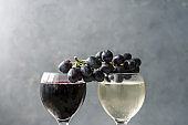 White and red wine in glasses with fresh blue grapes