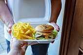 Woman takes delivered burger and french fries in a box from a man