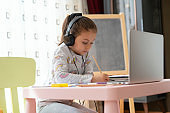 Little girl homeschooling and distance learning at home
