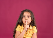 Cute little girl showing silent sign with finger on lips