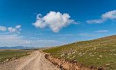 "Driving along a dirt road with fluffy cumulus clouds over the sky near Allahuekber Dağları, (which means ""Allahu Akbar Mountains"") in northeastern Turkey"