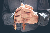 Praying hands with crucifix religious cross and rosary beads