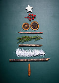 Christmas objects and decorations arranged into shape of Christmas tree over green wood background