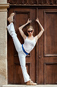 Young beautiful woman making strength exercises in front of an old fashioned wooden door