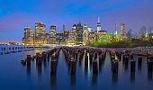 Night shot of wooden pillars in East river on Lower Manhattan, Brooklyn, New York