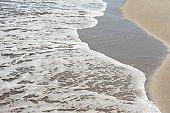 Sea waves running on the sandy beach, close-up