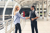 businesswoman and businessman with assistant shank hand greeting