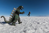 Woman playing in salt flats escaping from dinosaur
