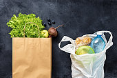 Zero waste concept.Paper bag with groceries and a plastic bag on dark background top view