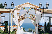 Luxurious, beautiful wedding arch with many flowers of roses near the classic columns on a background of blue sea or ocean. Summer wedding ceremony.
