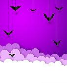 Black paper bats hanging on violet background.