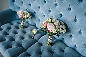 Two multi-colored wedding bouquets with peonies and roses lies on the background of a blue sofa. Wedding photography, bride and bridesmaid accessories.
