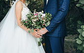 The bride in a white wedding dress and the groom in a blue plaid suit stand against each other and hold a large bouquet of white and pink roses with green foliage.