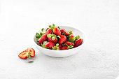 Heap of fresh strawberries in ceramic bowl on white background