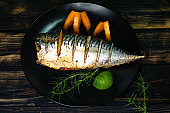 Mackerel baked to a golden crust, with lemon and rosemary in spices on a black matte plate. Proper nutrition. Diet. Health. Omega. Appetizing background.
