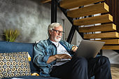 Modern elderly person place an order for purchase of goods online sitting on the couch at home Happy senior male smiling and looking at the laptop shopping online with credit card