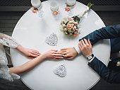 The bride and groom sit at a round white table and gently hold hands, showing wedding rings and a bouquet. Concept and composition. Wedding details, paper hearts.