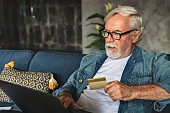 Portrait of man of retirement age shopping online on laptop pay with credit card Senior person place an order for a purchase of goods online