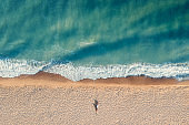 Aerial view of young woman with beautiful body lies alone on sandy beach with turquoise water Vacation travel and relax concept top view