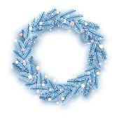 Frozen light blue fir wreath with bokeh lights.