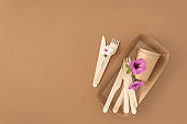 Pattern zero waste plastic free concept Disposable paper cups and plate with wooden forks and knives on beige background with copy space