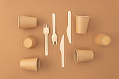 Disposable paper cups with wooden forks and knives on beige background Zero waste plastic free concept
