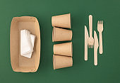 Zero waste, plastic free concept. Disposable paper cups with wooden forks and knives Eco sustainable living
