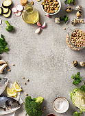 Frame of raw cooking ingredients for tasty and healthy food. Fresh fish, vegetables, herbs and legumes on gray background top view
