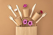 Paper bag with disposable paper cups plate wooden forks and knives on beige background Eco sustainable living Zero waste plastic free concept