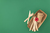 Frame of disposable paper cups and plate with wooden forks and knives on green background with copy space Pattern zero waste plastic free concept