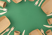 Frame of disposable paper cups and plate with wooden forks and knives on green background Pattern zero waste plastic free concept